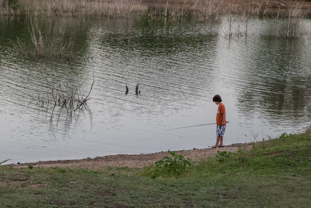 kid fishing on the shoreline by heather valey