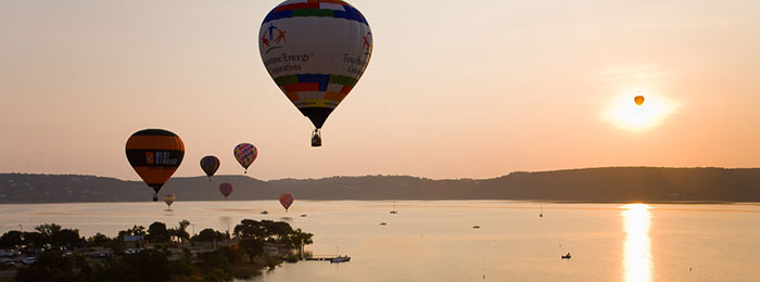 hot air balloons over the lake by unknown