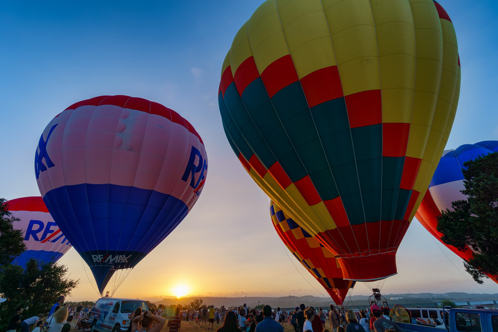 hot air balloons over crowd of people by jaco botha