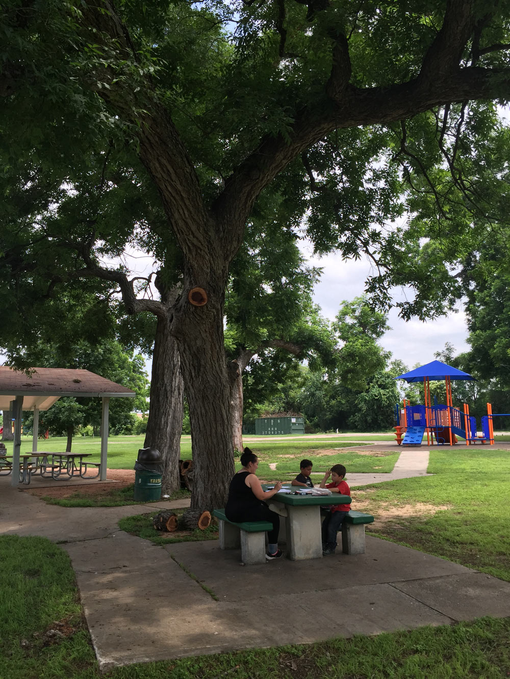 family on picnic table near playground and pavilion by dan pacatte